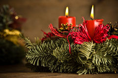 Burning christmas wreath. Green christmas wreath decorated with red burning candles, red ribbons and golden pine cones on timber floor royalty free stock photography