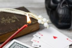 Burning church red candle in focus, blurred old holy bible, black skull and cards on wooden table. Misticism and fortune telling, royalty free stock image