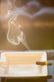 Burning cigar in ashtray Royalty Free Stock Photo