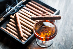 Burning cigar on humidor and cognac Stock Photo