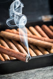 Burning cigar on humidor full with cigars Royalty Free Stock Image