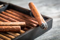 Burning cigar with smoke on wooden humidor Royalty Free Stock Photos
