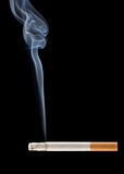 Burning cigarette. Cigarette smoke coming from a burning cigarette Royalty Free Stock Photo