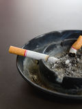 burning cigarette in ashtray and smoke on the table Royalty Free Stock Photo