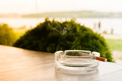 Burning cigarette in the ashtray on the wooden table against the background of the lake, people. On the beach and sunset Stock Photography