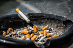 Burning Cigarette on Dirty Ashtray Royalty Free Stock Photo