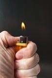 Burning cigarette lighter Stock Images