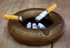 Burning cigarette on an old ashtray Stock Photo