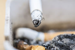 Burning cigarette. One Burning cigarette in an ashtray Royalty Free Stock Photos