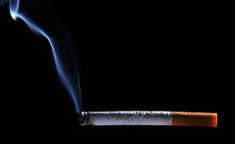 Burning cigarette over black background with smoke Royalty Free Stock Photography