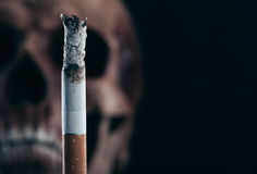 Burning cigarette with skull Stock Photos