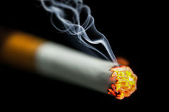 Burning cigarette with smoke Royalty Free Stock Photography