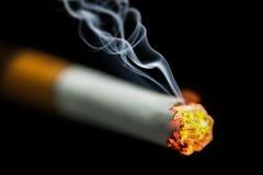 Burning cigarette with smoke. On black background Royalty Free Stock Photography