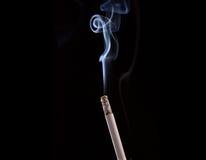 Burning cigarette with smoke Royalty Free Stock Image