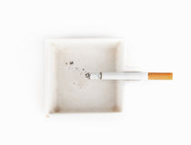 A burning cigarette in a white ashtray Royalty Free Stock Photography