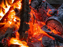 Burning coals of campfire. A close up view of red coals and flames of a hot, burning campfire Stock Image