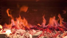 Burning coals in the stove are mixed creating a fiery dust. Slow motion. stock footage