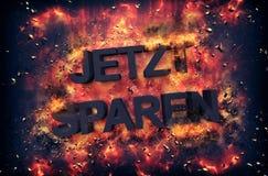 Burning coals surrounding the word Jetzt Sparen Stock Image
