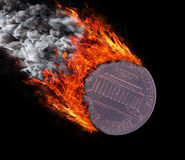 Burning coin with a trail of fire and smoke Royalty Free Stock Images