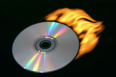 Burning compact disc. Compact disc with a tail of fire on a black background Stock Image