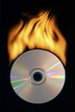 Burning compact disc. Compact disc with a tail of fire on a black background Royalty Free Stock Images
