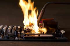 Burning computer main board. In rusty background. Copyspace Stock Photo