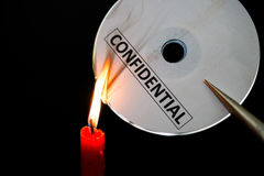 Burning a confidential compact disc with candle. In dark Royalty Free Stock Photos
