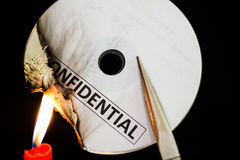 Burning a confidential compact disc with candle. In dark Stock Photos