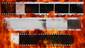 Burning and damaged strip of celluloid film. Burning dirty, messy and damaged strip of celluloid film Royalty Free Stock Photography