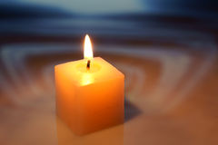 Burning decorative candle. The burning decorative candle, is photographed on an abstract background Stock Images