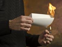 Burning document. Man holding butane lighter to folded document Stock Images