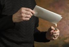 Burning document_2. Man holding butane lighter to folded document Royalty Free Stock Photography