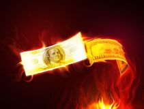 Burning dollar. The money covered with a flame flying above the ground Royalty Free Stock Photography