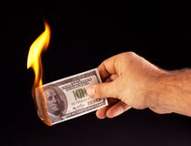 Burning dollar in hand. Royalty Free Stock Image