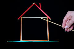 Burning down the house. House outline made from colored matchsticks, symbolizing arson or fire hazard Stock Image