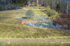 Burning dry grass. Dry last year's grass burning in the spring on the earth Stock Photography