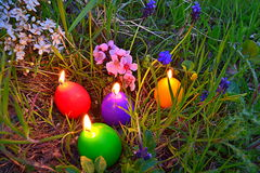 Burning Easter eggs candles in green grass Royalty Free Stock Photo