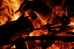 Burning Embers on Fire. A detail of an outdoor campfire, bonfire a closeup of the burning embers and ,dark burning logs and sticks Royalty Free Stock Photo