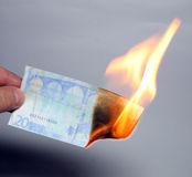 Burning euros. Hand holding burning money Stock Image
