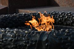 Burning fire closeup of eternal flame of monument in Odessa city park of Ukraine. Bright orange flames inside bronze sculpture. Fire texture abstract background royalty free stock images