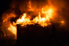 Burning fire flame on wooden house roof Stock Photos