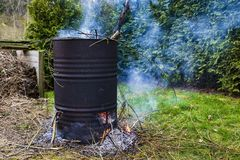 A burning fire of garden waste in an old barrel. royalty free stock photography