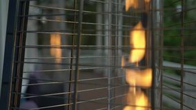 Burning fire in a gas outdoor heater working on terrace. Steel metal pyramid.