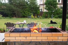 Burning fire in the grill. Backyard Patio Area with Fireplace and Furniture. Green Party area royalty free stock photos