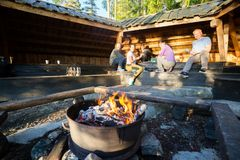 Burning Firepit With Friends Preparing Food In Shed. Flames in firepit with multiethnic friends preparing food in shed at forest during hiking Royalty Free Stock Photos