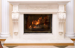 Burning fireplace as a piece of furniture Royalty Free Stock Photos