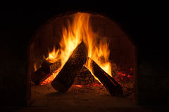 Burning fireplace, classic style interior detail. Warm cosy home, glowing flame closeup, atmosphere of comfort and relaxation royalty free stock images