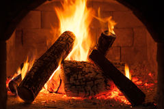 Burning fireplace, classic style interior detail. Warm cosy home, glowing flame closeup, atmosphere of comfort and relaxation stock photo