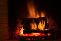 Burning fireplace with fresh firewood Stock Photo