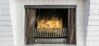 Burning fireplace with iron curtains in closeup winter background royalty free stock images